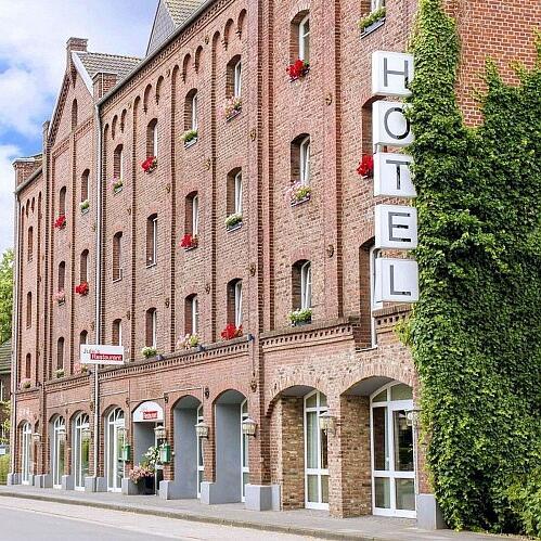 Ein großes Gebäude mit roten Backsteinen und dem Werbeschild Hotel
